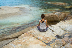 La muchacha que reflexiona sobre piedras por el mar, el préstamo de la muchacha con yoga la isla Samui, yoga en Tailandia Fotografía de archivo libre de regalías