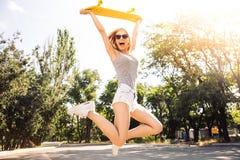 La muchacha que salta con el monopatín Fotos de archivo libres de regalías