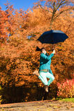 La muchacha que salta con el paraguas azul en parque otoñal Fotos de archivo libres de regalías