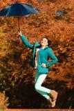 La muchacha que salta con el paraguas azul en parque otoñal Fotos de archivo