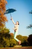 La muchacha que salta con el paraguas azul en parque otoñal Foto de archivo libre de regalías