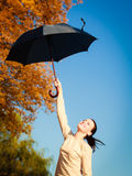La muchacha que salta con el paraguas azul en parque otoñal Imagen de archivo