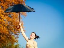 La muchacha que salta con el paraguas azul en parque otoñal Imagen de archivo libre de regalías