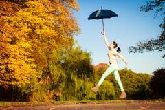 La muchacha que salta con el paraguas azul en parque otoñal Imagenes de archivo