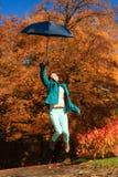 La muchacha que salta con el paraguas azul en parque otoñal Fotografía de archivo