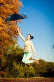 La muchacha que salta con el paraguas azul en parque otoñal Foto de archivo