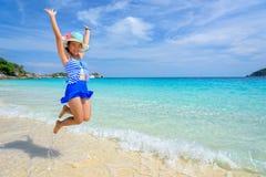 La muchacha que salta con feliz en la playa en Tailandia Fotos de archivo libres de regalías