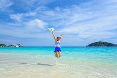 La muchacha que salta con feliz en la playa en Tailandia Foto de archivo libre de regalías