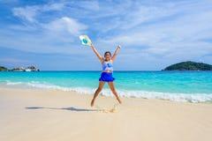 La muchacha que salta con feliz en la playa en Tailandia Foto de archivo