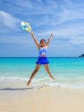 La muchacha que salta con feliz en la playa en Tailandia Imagenes de archivo