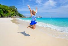 La muchacha que salta con feliz en la playa en Tailandia Imagen de archivo libre de regalías