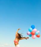 La muchacha que salta con los globos coloridos en fondo del cielo Foto de archivo