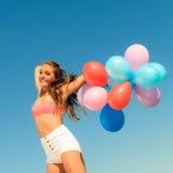 La muchacha que salta con los globos coloridos en fondo del cielo Fotos de archivo libres de regalías