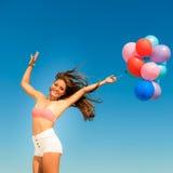 La muchacha que salta con los globos coloridos en fondo del cielo Fotografía de archivo libre de regalías