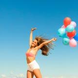 La muchacha que salta con los globos coloridos en fondo del cielo Imagen de archivo