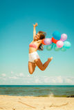 La muchacha que salta con los globos coloridos en la playa Foto de archivo