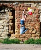 La muchacha que salta con los globos en fondo del grunge Fotografía de archivo
