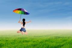 La muchacha que salta con un paraguas Fotografía de archivo