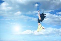 La muchacha que salta contra el cielo azul Imágenes de archivo libres de regalías