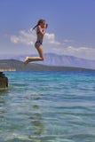 La muchacha que salta de un embarcadero de madera en el mar Imágenes de archivo libres de regalías