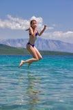 La muchacha que salta de un embarcadero de madera en el mar Fotografía de archivo