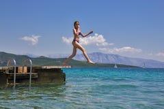 La muchacha que salta de un embarcadero de madera en el mar Fotos de archivo libres de regalías