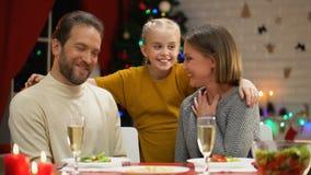 La muchacha que salta debajo de la tabla y que asusta a los padres, todos que ríen y que abrazan, víspera de Navidad metrajes
