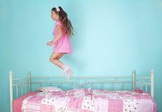 La muchacha que salta en cama Imagen de archivo libre de regalías