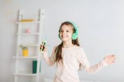 La muchacha que salta en cama con smartphone y los auriculares Imagenes de archivo