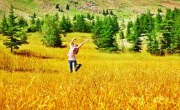 La muchacha que salta en campo de trigo Imagen de archivo