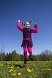 La muchacha que salta en campo del diente de león Foto de archivo libre de regalías