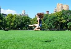 La muchacha que salta en Central Park, Nueva York Imagen de archivo libre de regalías