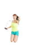 La muchacha que salta en el aire con los auriculares que muestran los pulgares para arriba Imagen de archivo