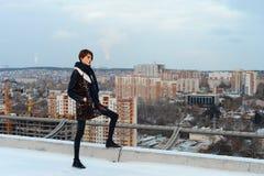 La muchacha que salta en el tejado en la ciudad Fotografía de archivo libre de regalías