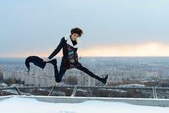 La muchacha que salta en el tejado en la ciudad Foto de archivo