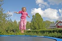 la muchacha que salta en el trampolín Fotos de archivo