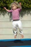 La muchacha que salta en el trampolín foto de archivo libre de regalías