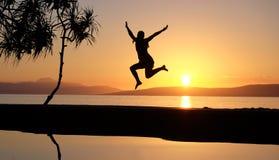 La muchacha que salta en el waterpool en la playa contra la puesta del sol Foto de archivo libre de regalías