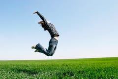 La muchacha que salta en fondo natural Foto de archivo libre de regalías