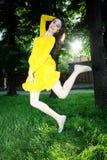 La muchacha que salta en la hierba. Imagen de archivo libre de regalías