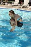 La muchacha que salta en la piscina Imagen de archivo libre de regalías