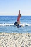 La muchacha que salta en la playa Fotografía de archivo libre de regalías