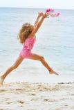 La muchacha que salta en la playa de la arena Fotos de archivo libres de regalías