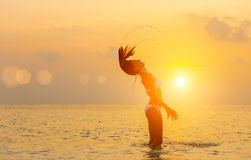 La muchacha que salta en la playa en la puesta del sol Imagenes de archivo