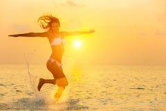 La muchacha que salta en la playa en la puesta del sol Foto de archivo libre de regalías