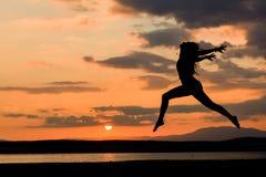 La muchacha que salta en la puesta del sol por el agua Fotografía de archivo