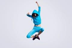 La muchacha que salta en suéter con capucha Imágenes de archivo libres de regalías