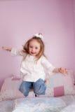 La muchacha que salta en su cama Imagen de archivo libre de regalías