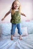 La muchacha que salta en su cama Fotos de archivo