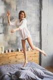 La muchacha que salta en su cama en camisa foto de archivo libre de regalías